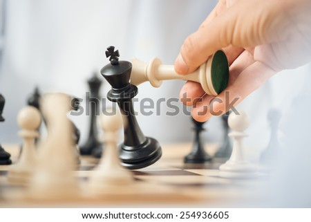 Close-up of human hand holding a white chess king over the chessboard, while crashes black chess king. - stock photo