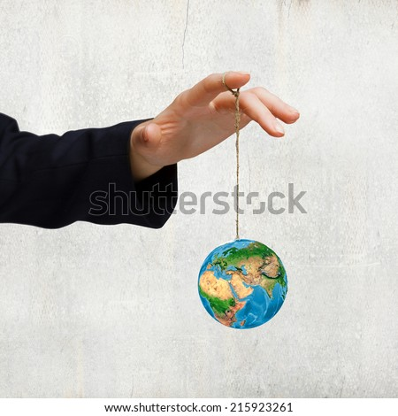 Close up of human hand holding Earth planet on rope. Elements of this image are furnished by NASA - stock photo