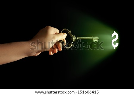 Close-up of human hand holding key. Money concept - stock photo