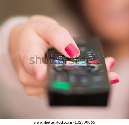 Close-up Of Human Hand Holding Remote - stock photo