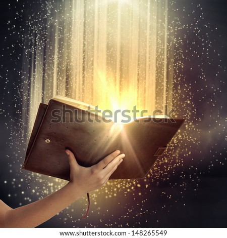 Close up of human hand holding saint book - stock photo