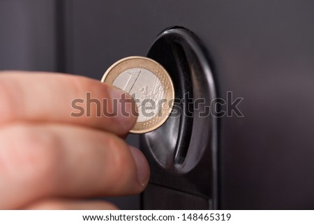 Close-up of human hand inserting coin in vending machine - stock photo