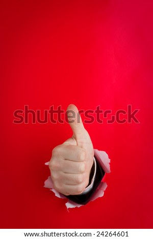 Close up of human hand making thumbs up sign protruding through hole in red background.