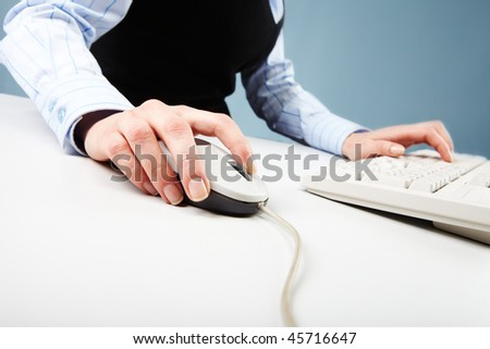 Close-up of human hand on white mouse during computer work - stock photo