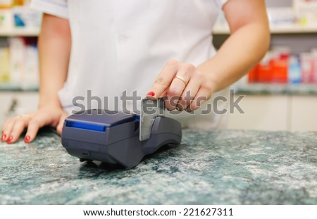 Close up of human hand putting credit card into payment machine in drug store - stock photo