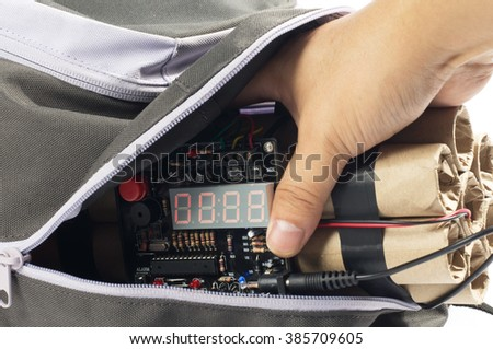 Close-up of human hand taking time bomb from backpack. - stock photo