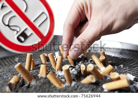Close up of human hand with cigarette butts stuck in ash with no smoking sign in background. - stock photo