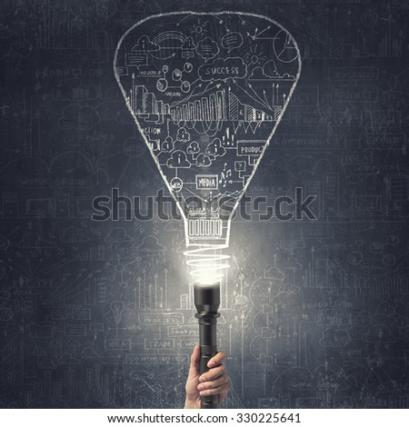 Close up of human hand with lantern and business sketches on wall - stock photo