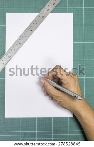 Close up of human hand with pen on white paper - stock photo