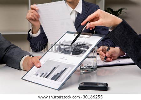 Close-up of human hand with pen pointing at document while explaining something - stock photo