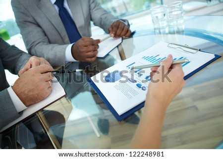 Close-up of human hand with pen pointing at paper while explaining something to colleagues - stock photo