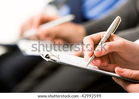 Close-up of human hand with pen writing something