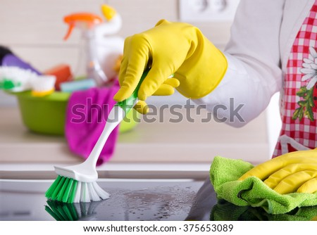 Close up of human hand with protective gloves cleaning induction hob with scrubbing brush and rag. Cleaning supplies in background - stock photo