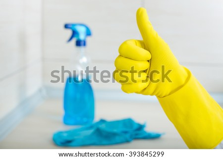 Close up of human hand with yellow rubber glove showing ok sign against spray bottle and cloth on clean kitchen countertop - stock photo