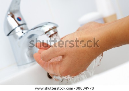 Close-up of human hands being washed under stream of pure water from tap - stock photo