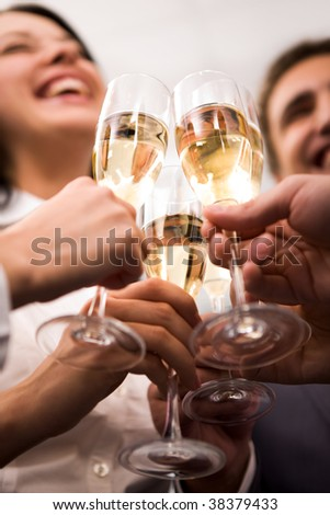 Close-up of human hands cheering up with flutes of golden champagne