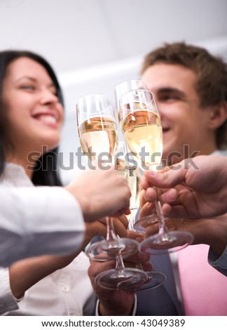 Close-up of human hands cheering up with flutes of golden champagne - stock photo