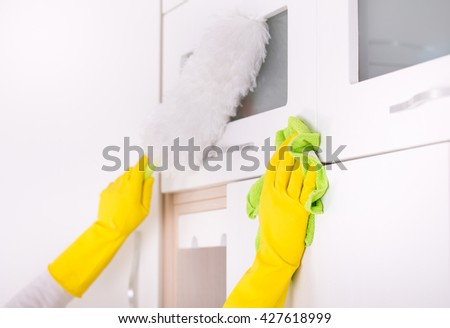Close up of human hands cleaning and dusting kitchen cabinets - stock photo