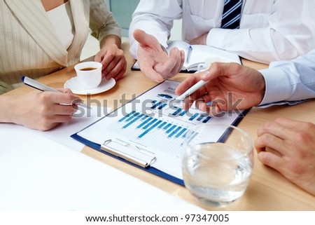 Close-up of human hands during discussion of business documents at meeting - stock photo