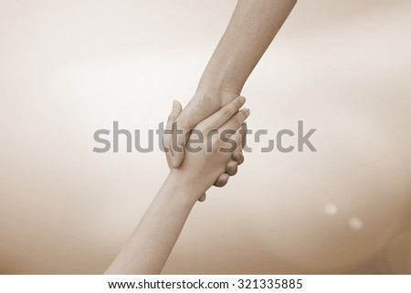 close up of human hands holding together for helping:helping hands concept :religion  concept.hand of god concept.abstract helping hand in sepia vintage tone colors concept. - stock photo