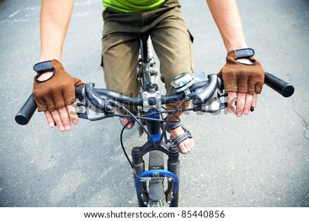 Close-up of human hands on handlebar - stock photo