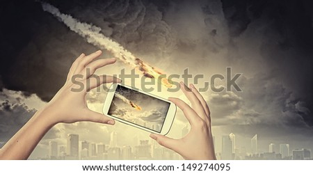 Close up of human hands taking photo of falling meteorite