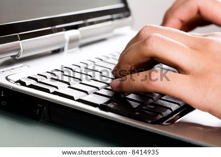 Close-up of human hands typing a text on the laptop
