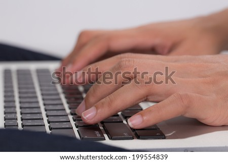 Close-up of human hands typing on the keyboard - stock photo