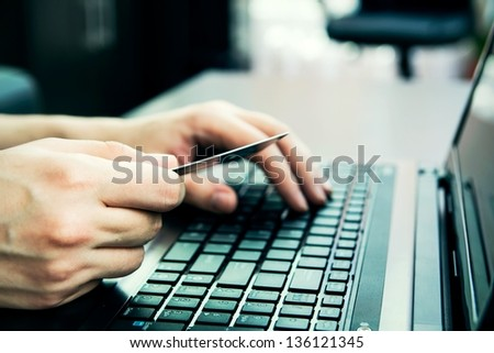 Close-up of human hands with credit card on keyboard - stock photo