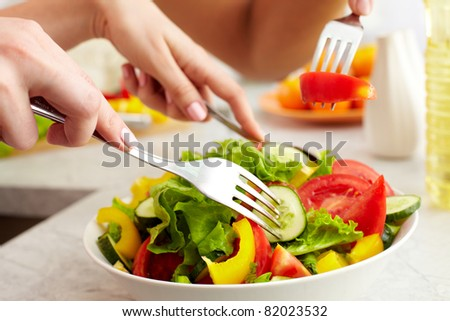 Close-up of human hands with forks tasting salad - stock photo