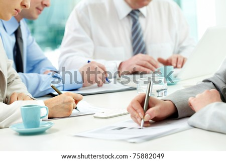 Close-up of human hands with pens over financial documents
