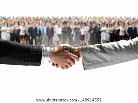 Close-up of human handshake with crowd of people at background