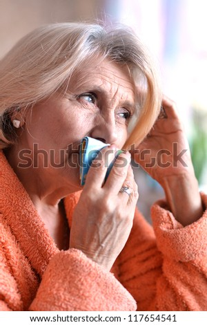 Close-up of ill elderly woman touching her head - stock photo