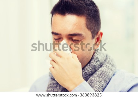 close up of ill man with flu blowing nose at home - stock photo