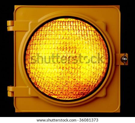 Close up of illuminated amber traffic light lens - stock photo