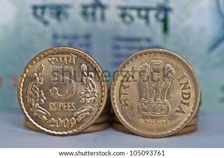 Close up of Indian Coin, 5 rupees, out of focus 100 rupees note in background, isolated, copy space, - stock photo