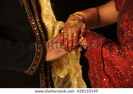 Close up of Indian couple's hands at a wedding