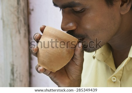 Close-up of Indian mid adult man having morning tea in traditional cup made of mud - stock photo