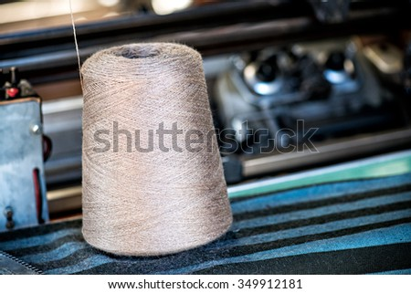 Close Up of Industrial Sized Spool of Silver Gray Thread in near Sewing Machine in Industrial Manufacturing Warehouse Setting - stock photo