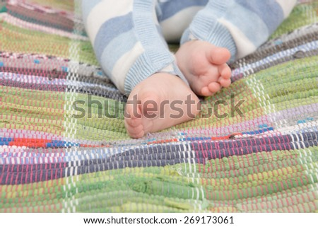 Close up of infant baby feel on colored mat - stock photo