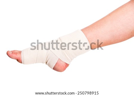 Close-up of injured ankle with bandage on a white background. - stock photo