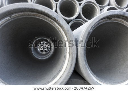 Close up of inside of concrete pipe with other pipes of various sizes behind - stock photo
