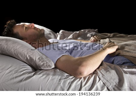 close up of insomniac unable to sleep in bed - stock photo