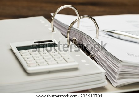 Close-up Of Invoice With Calculator And Pen On Desk - stock photo