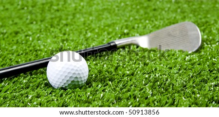 Close up of Iron golf club on green grass(artificial turf) at low angle - stock photo