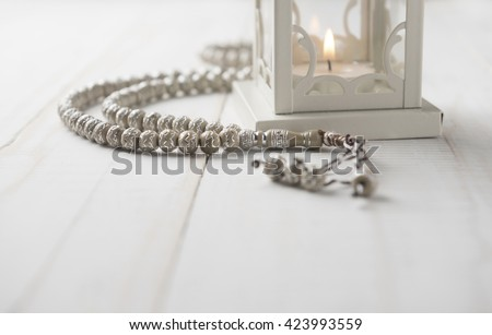 Close up of Islamic prayer beads near candle holder on white background. - stock photo