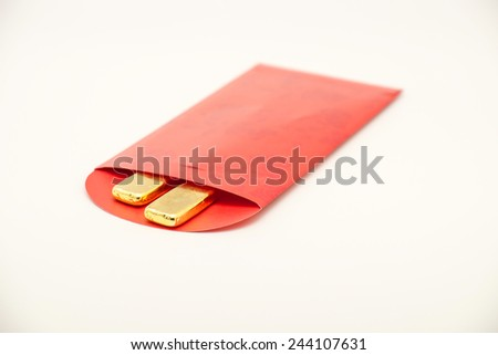 Close up of isolated pure gold bar on red packet for giving during Chinese Lunar Year on white background - stock photo