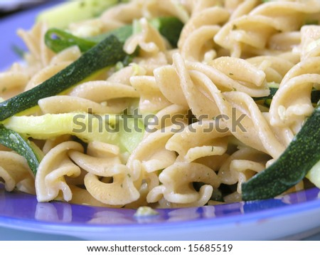 Close up of italian  integral pasta with zucchinis .Shallow DOF - stock photo