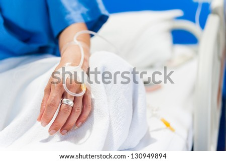 close up of iv drip in woman hand on bed in hospital