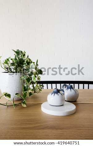 Close up of ivy pot plant and ornaments on a contemporary wooden dining table